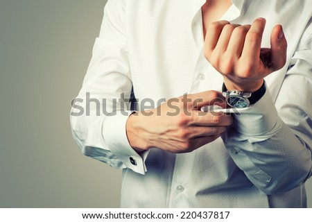 Sexy man buttons cuff-link on French cuffs sleeves luxury white shirt. Tonal correction - stock photo