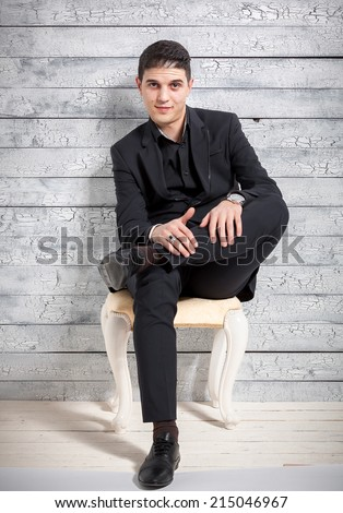 Sexy man in suit sitting on chair with legs crossed at studio - stock photo