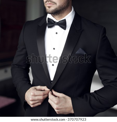 Sexy man in tuxedo and bow tie posing - stock photo