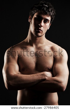 sexy man with naked torso posing against dark background - stock photo