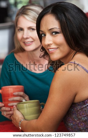 Sexy mature Native American woman sitting with blond friend in cafe - stock photo