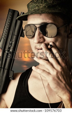 sexy military man wearing fashionable sunglasses and cap with automatic smoking a cigar - stock photo
