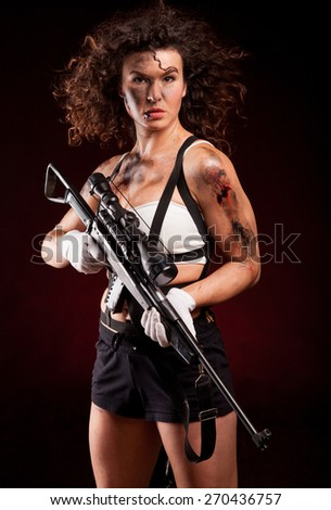 Sexy military woman posing with sniper gun. With blood, dirty face and wound. - stock photo