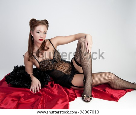 Sexy model in lingerie sitting on floor on red satin - stock photo
