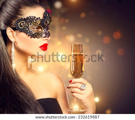 Sexy model woman with glass of champagne wearing venetian masquerade mask at party, drinking champagne over holiday glowing background. Christmas and New Year celebration - stock photo