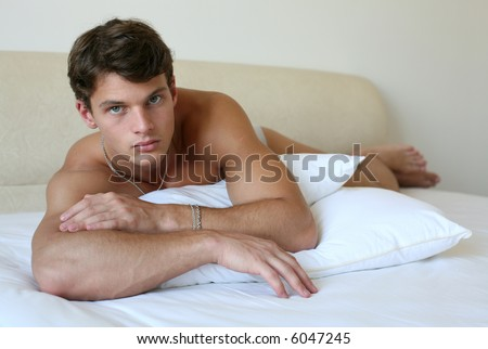 Sexy muscular man lying on the bed - stock photo