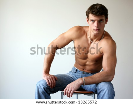 Sexy muscular man sitting on the chair. Copy space - stock photo
