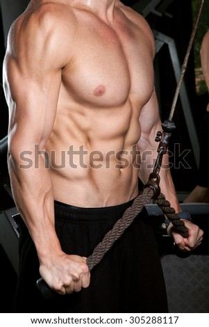 Sexy muscular man working out in gym, shaped abdominal. Strong male naked torso abs - stock photo