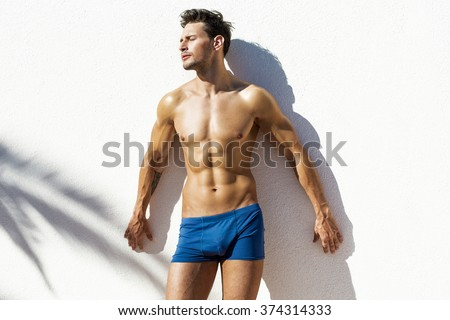 Sexy muscular model in beach shorts  - stock photo