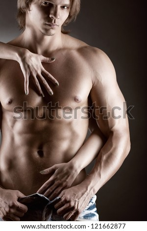 Sexy muscular naked man and female hands unbuckle his jeans on a dark background - stock photo