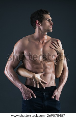 Sexy muscular shirtless man and female hands holding his chest - stock photo