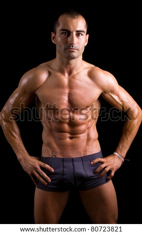 Sexy muscular young man against black background - stock photo