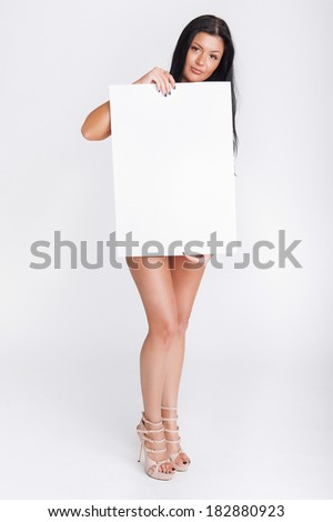 Sexy naked girl holding a vertical blank board for text - stock photo