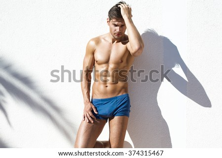 Sexy naked model with athletic body wearing blue beach shorts and posing on white wall - stock photo