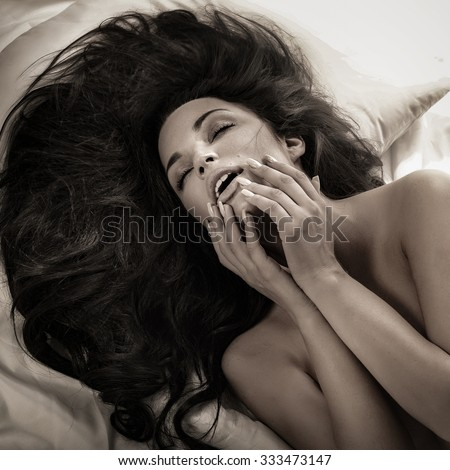 Sexy naked woman lying in bed, relaxing. Brunette sensual lady. - stock photo