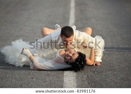 Sexy passion between bride and groom on countryside road - stock photo