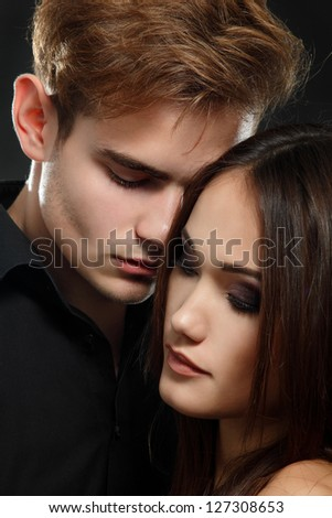Sexy passion couple, beautiful young man and woman closeup, studio shot over black - stock photo
