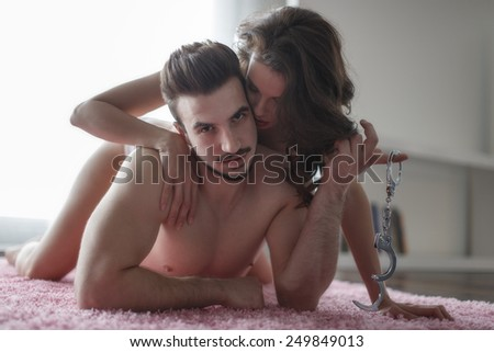 Sexy passionate couple on the carpet with handcuffs at morning, foreplay - stock photo
