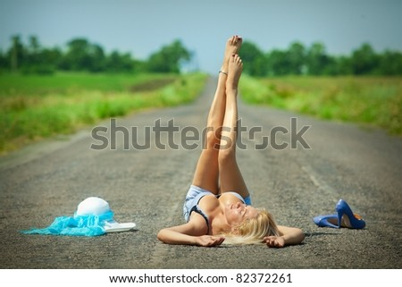 Sexy passionate woman lying on a desert road - stock photo