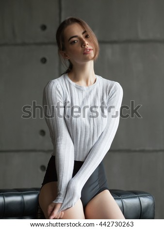 sexy passionate young woman with long brunette red hair in front of the window in grey shirt and black pants - stock photo