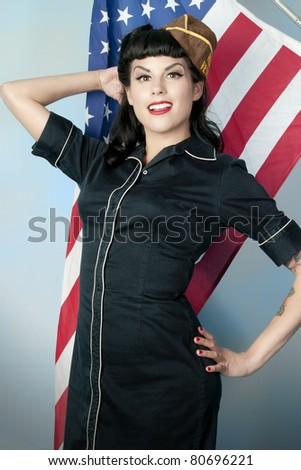 Sexy patriotic pin up model in front of American flag - stock photo