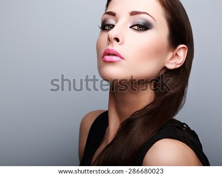 Sexy perfect makeup woman looking with smoky eyes and pink lips on blue background. Closeup portrait - stock photo
