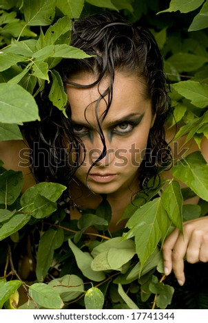 Sexy photo of a brunette posing with her head peaking out of a bunch of leaves - stock photo