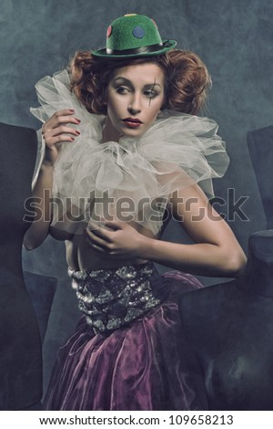 Sexy Pierrot woman among the mannequins - stock photo