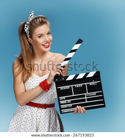 Sexy pin-up girl holding a Clapper board. Film-making or film production concept / photo set of young American pin-up model on blue background - stock photo