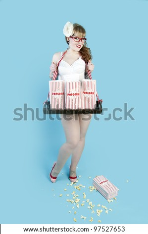 Sexy pin up model selling popcorn in paper bags - stock photo
