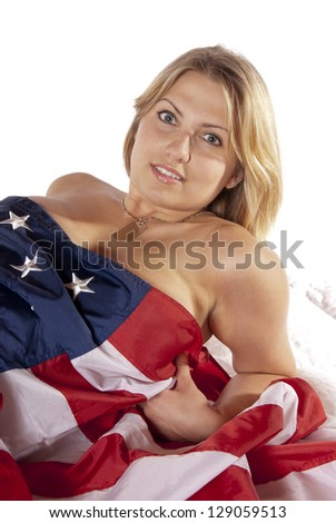 Sexy pinup calendar girl young woman implied nude wrapped American Flag looking into the camera seductively. Patriotic, for the holidays fourth of July, independence day, flag day, veterans day - stock photo