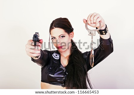 Sexy police woman holding a gun and handcuffs - stock photo