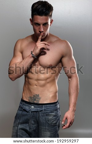 Sexy portrait of a very muscular shirtless male model against grey wall in sensual pose .Low light. - stock photo
