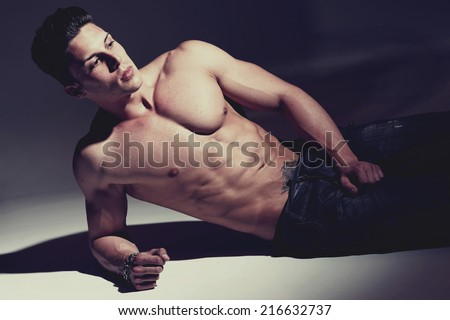 Sexy portrait of a very muscular shirtless male model against white wall in sensual pose - stock photo