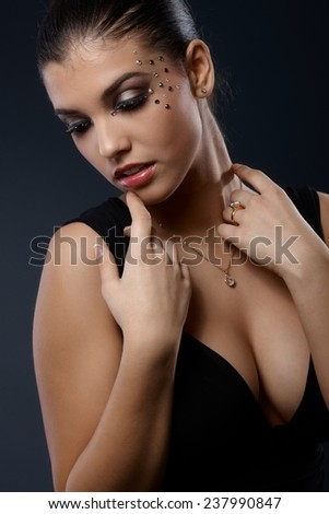 Sexy portrait of woman posing in seductive black dress with cleavage in fancy makeup with strasses. - stock photo