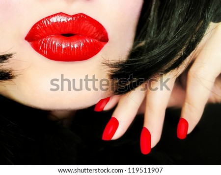 Sexy pretty woman with black hair, red lips and fingernails sending a kiss / smooch - closeup - stock photo