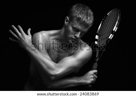 Sexy racket. A portrait of a tanned sportive tennis player with a racket against black background. - stock photo