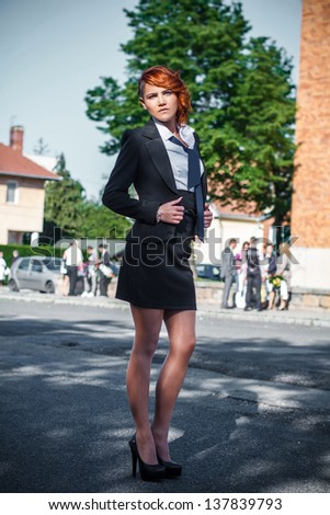 Sexy redhead student posing at school - stock photo