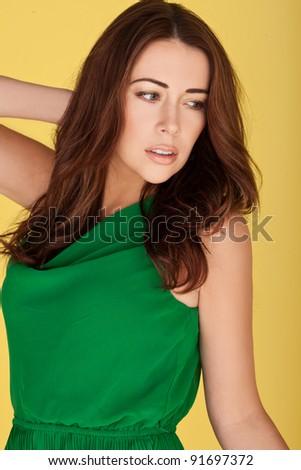 Sexy redhead woman wearing emerald green dress against yellow studio background. - stock photo