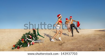 Sexy Santa pulling Christmas tree on a sled at the beach.  (concept: Tropical winter fun) - stock photo