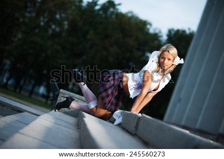 Sexy schoolgirl posing on stairs outdoors - stock photo