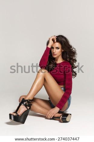 Sexy seductive woman sitting on the floor - stock photo