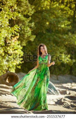 sexy sensual very beautiful brunette girl with long hair in a green dress goes on the sand - stock photo