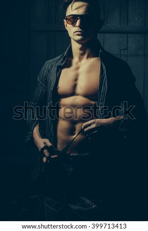 Sexy serious sensual muscular young macho man with bare torso and stylish hair in shirt sun glasses and bag standing indoor on wooden background, vertical picture - stock photo