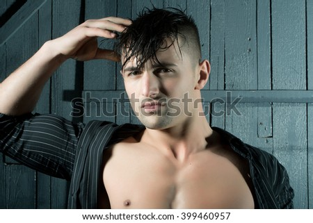 Sexy serious sensual muscular young macho man with bare torso and wet hair in shirt standing with raised hands indoor on wooden background, horizontal picture - stock photo