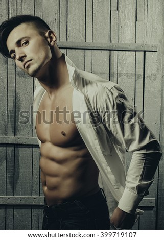 Sexy serious sensual muscular young macho man with bare torso in white shirt standing indoor on wooden background, vertical picture - stock photo