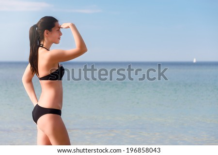 Sexy shapely young woman in a black bikini standing sideways with her hand raised to her forehead looking out over the ocean with copyspace - stock photo