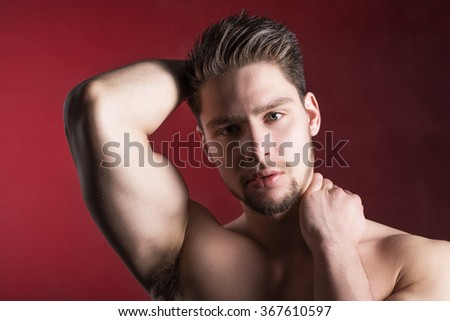 Sexy shirtless male model against red background - stock photo