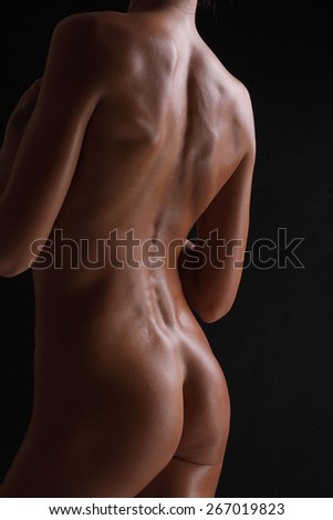sexy silhouette of a naked female back and buttocks - stock photo