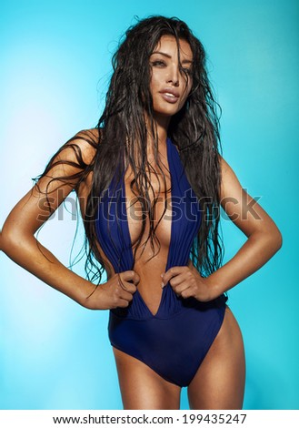 Sexy slim brunette woman posing in fashionable blue swimsuit , looking at camera. Girl with long wet hair. Blue background. - stock photo